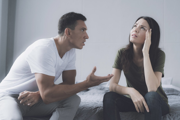 Мужчина и женщина сидят на краю кровати и ругаются | Премиум Фото