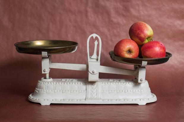 белые весы с яблоками на чаше