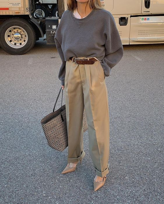 a white tee, a graphite grey oversized jumper, tan oversized pants, beige shoes and a printed bag